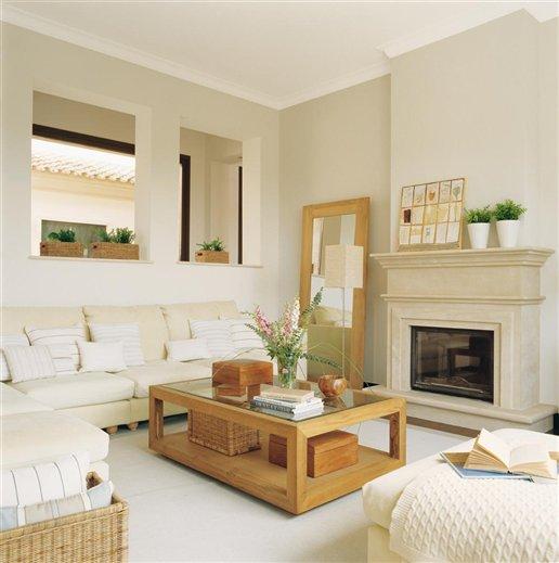Salón con sofás en color crudo y chimenea