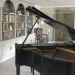 Poryecto de reforma e interiorismo Melodía por Estudio de interiores Libia Bárcenas | salón con librería y piano